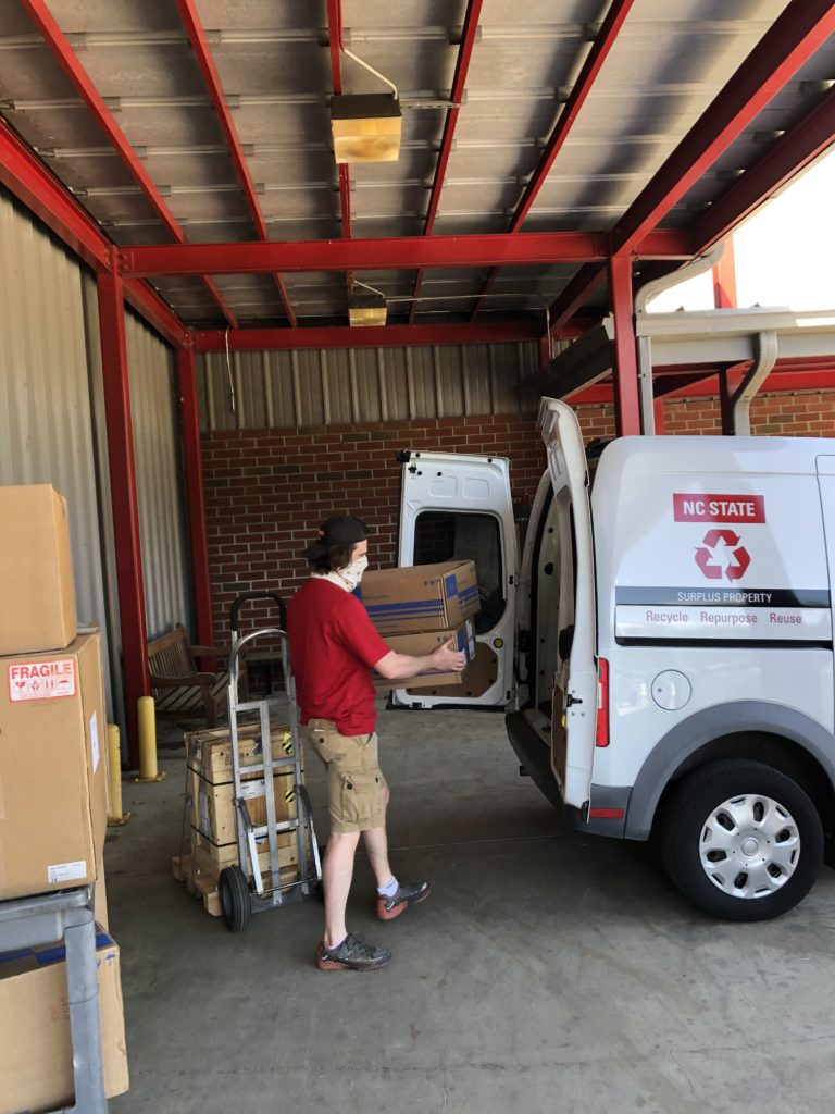 Worker loading a surplus truck with packages